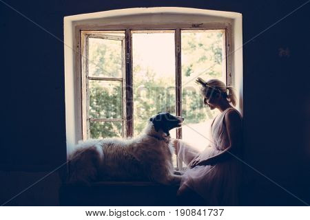 Beautiful young woman wearing fairy costume and playing with her dog
