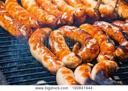 Many original Thuringian frying sausages on the wood coal grill