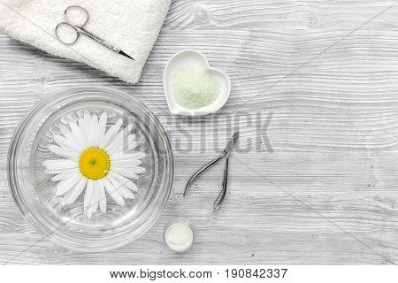 Spa composition on wooden desk with salt, chamomile, towel and manicure set copyspase top view.