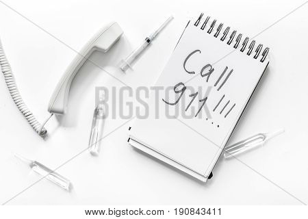 The words Call 911 written in a notebook on white background top view.