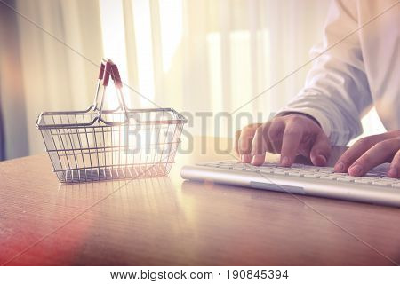 E-commerce concept. Man's hands typing on computer keyboard next to a shopping cart. Concept of online shopping and e-commerce, for background, website banner, promotional materials, presentation templates, advertising.