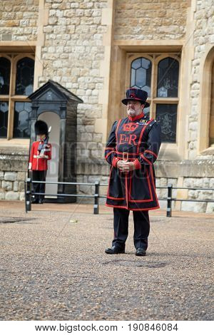 London, UK - 7 June 2017: A Beefeater, or Yeoman Warder of the Tower of London in full undress uniform, with a Coldstream Guard in the Sentry Box behind.