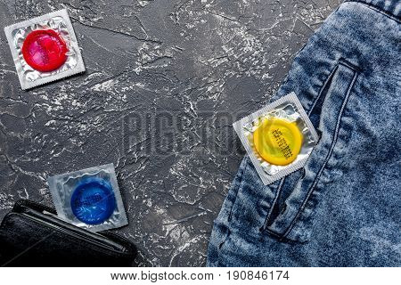 condoms and wallet for male contraception and birth control on dark background top view