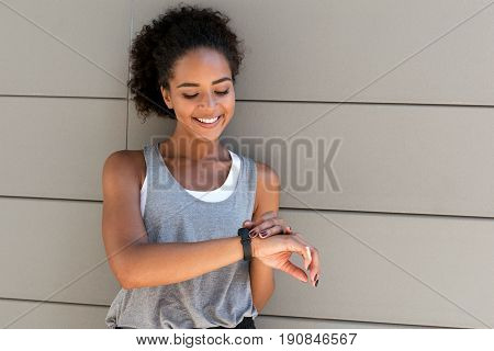 Young smiling woman checking her activity tracker