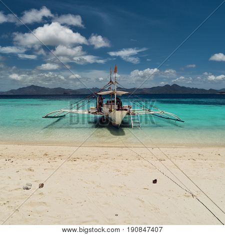 Palawan - May 2017: Boat by tropical island surrounded by turquoise sea.