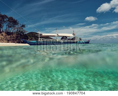 Palawan - May 2017: Boat by tropical island surrounded by turquoise sea. Partly underwater shot.