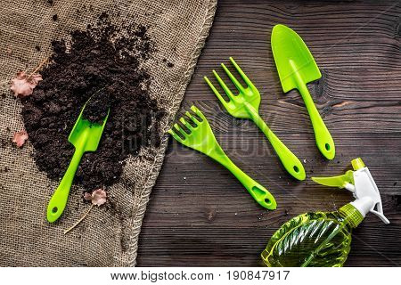 green equipment with rake, trowel, ground for planting greenary in summer on woden desk background top view