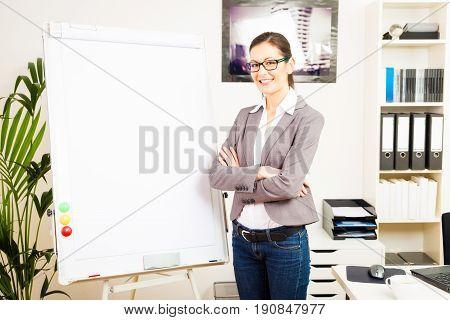 businesswoman standing next to an empty flipchart