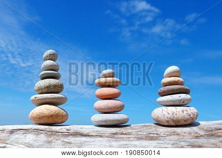 three pyramids of colored pebbles on a background of blue sky. Balance and poise stones.