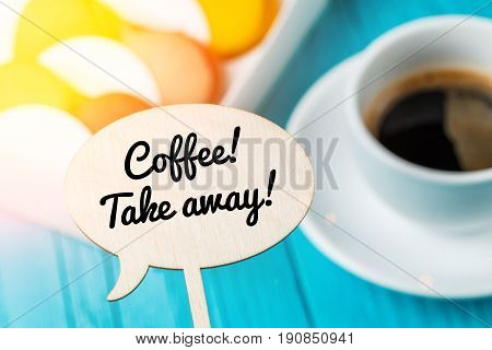 Photo of wooden plaque with inscription, macaroons, cup of coffee