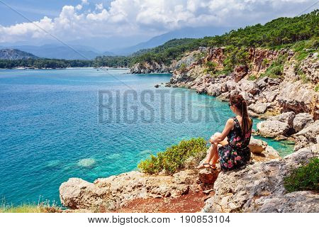 Tourist Girl Sitting And Looking On Bay Of Old Greek Town Phaselis. Panoramic View On Coast Near Kem