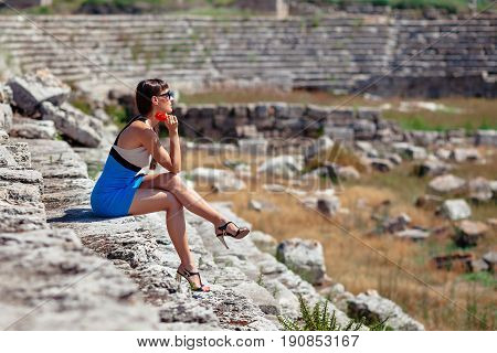 Pretty Tourist Woman With Red Flower In Creative Dress Ans High Heels At The Ruins Of Ancient City O