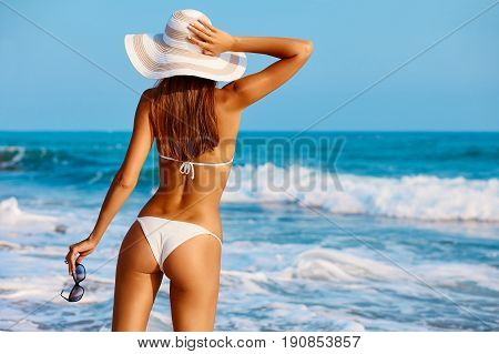 Sexy Back Of A Beautiful Woman In White Bikini And Hat On Sea Background. Sporty Buttocks.