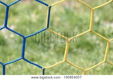 Detail Of Yellow Blue Crossed Soccer Football Net With Grass