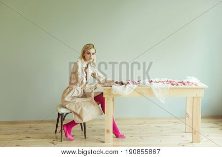 A beautiful blond woman in a beige trench coat pink tights and pink shoes sits sitting on a chair near a wooden table. Fashion model. Fashion photo concept