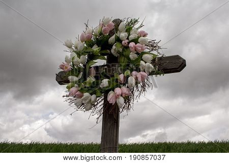 Simple Wooden Cross with a Wreath of White and Pink Silk Tulips