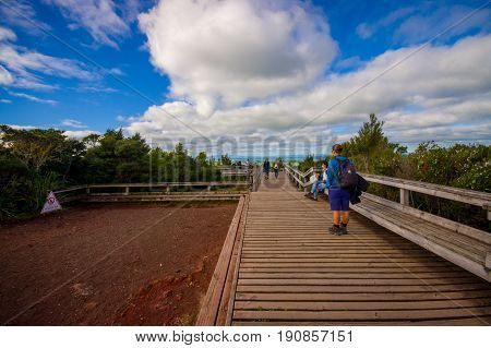AUCKLAND, NEW ZEALAND- MAY 12, 2017: Unidentified people enjoying the beautiful view from top in the mountain in Rangitoto Island walking in wooden paths, New Zealand in a sunny day.