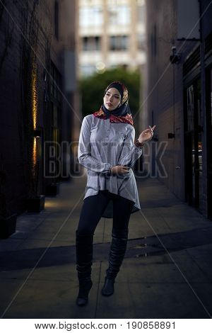 Woman wearing conservative Hijab fashion while walking in a modern urban city. The image depicts muslims who are proud to wear traditional clothing. The female wearing religious outfit represents individualism feminism and ethnic and racial acceptance.