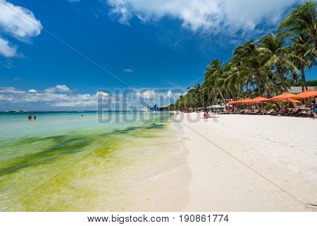BORACAY, WESTERN VISAYAS, PHILIPPINES - MARCH 26, 2017: Nice tents beach front full of tourists having a great day in the White Beach at Boracay. Water plants makes the water green.