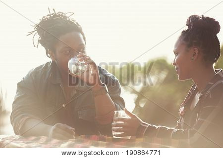 black guy with dreads taking a sip of his alcoholic beverage while on a date with an attractive multi ethnic woman whom looks like she is enjoying his conversation.