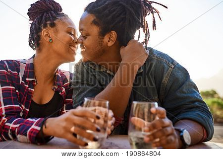 Interracial couple on a date outdoors with drinks sitting at a table during golden hour before sunset about to kiss for the first time by her new life partner and lover.