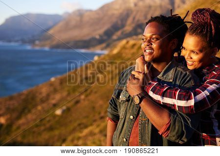 Happy mixed race couple smiling while looking sideways out towards the stunning view of the oceans and mountains in the surrounding landscape, while the woman hold the man from behind.