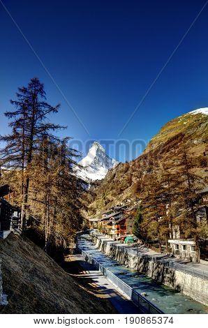 The Matterhorn in Switzerland with a blue sky and a stream running through Zermatt.