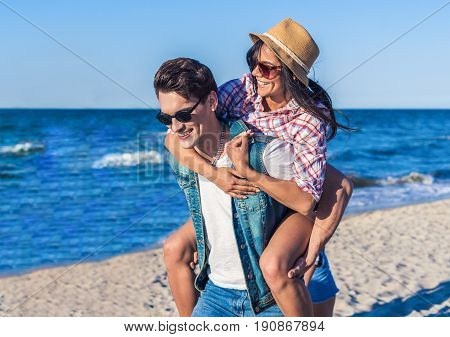 young funny couple in sunglasses piggybacking on the beach. Sea is on background. Girl is wearing hat. they look happy