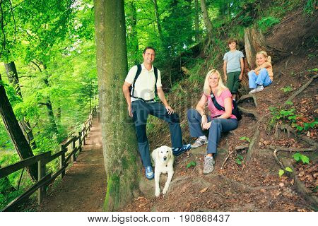 family of four hiking outdoors, enjoying summer.