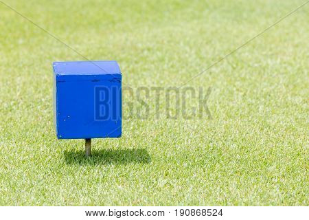 Close-up blue color wooden tee off area or tee box with natural green golf course in background.