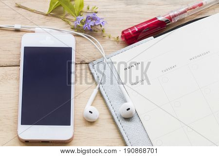 notebook monthly and mobile for business on background wood