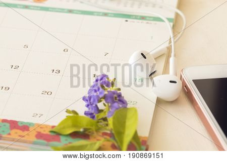calendar and mobile with earphone on background white
