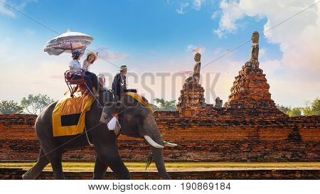 NOVEMBER 4 2016: Tourist with an elephant at wat Chaiwatthanaram temple in Ayuthaya Historical Park a UNESCO world heritage site
