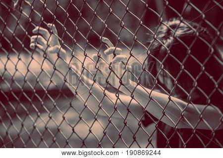 teen behide the cage or woman jailed unhappy girl hand sad hopeless at fence prison in jail no free and freedom struggle teen concept.
