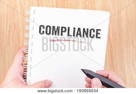 Compliance Word On White Ring Binder Notebook With Hand Holding Pencil On Wood Table,business Concep