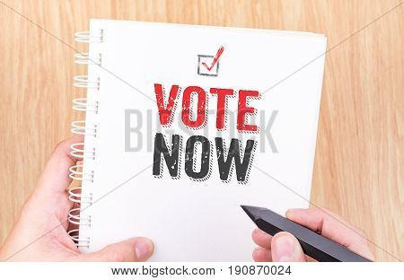 Vote Nowe Word On White Ring Binder Notebook With Hand Holding Pencil On Wood Table,business Concept