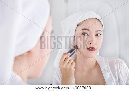 Woman Looking In The Mirror And Applying Cosmetic With Brush