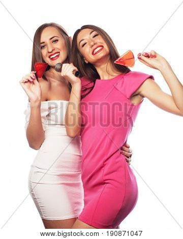 Happy girls friends with microphone and candy over white background