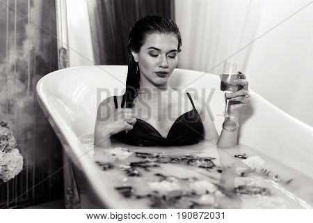 Side view of Sexy brunette woman relaxing in a hot bath with flowers and champagne in hand. she is wearing black sexual lingerie. woman in bath. Her eyes are closed. black and white photo. bw