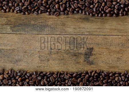 Stack of roast coffee beans. Copy space of rustic wood table line on top and below with coffee beans. Roast coffee beans on wood table for background and wallpaper. Roast coffee bean background. Black coffee bean wallpaper with copy space.