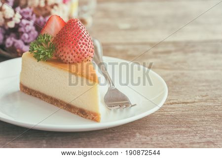 Homemade strawberry cheese cake on white plate decorated with strawberry and parsley. Moist and smooth classic style baked cheese cake. Copy space background of delicious strawberry New York cheese cake. Strawberry cheese cake on table.