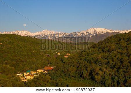Full moon over the mountains landscape near Talgar peak Tien-Shan Almaty Kazakhstan.