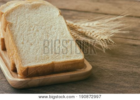 Sliced bread stack on wood plate. Homemade bread for breakfast put on rustic wood table. Soft and sticky homemade bread for delicious toast in breakfast. Homemade bakery background with copy space. Delicious homemade bread in warm tone.