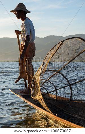 Inle Lake Myanmar - December 7 2014: Burmese fishermen on boat with fishing net at Inle lake in Myanmar (Burma)