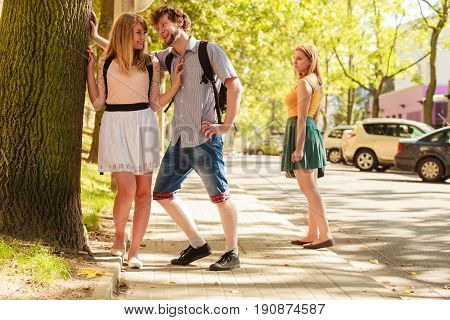 Jealous Girl Looking At Flirting Couple Outdoor.