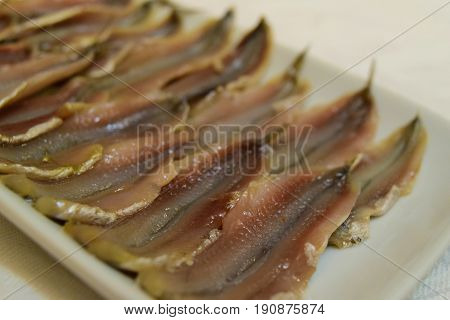 Headless marinated anchovy fish fillet in ceramic plate on white tablecloth background