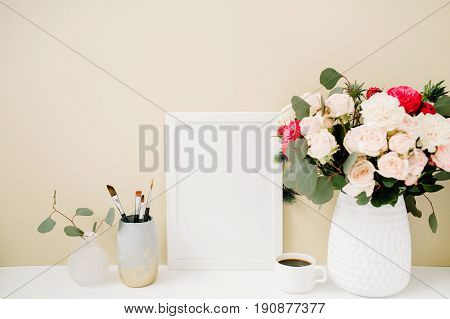 Home office desk with photo frame mockup beautiful roses and eucalyptus bouquet in front of pale pastel beige background. Blog website or social media concept .