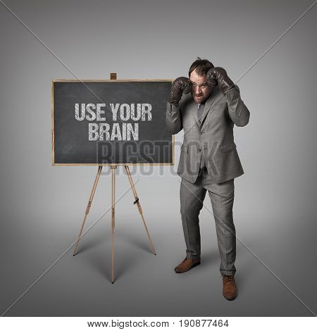 Use your brain text on blackboard with businessman with boxing gloves