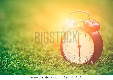 Times Retro Clock Lay On Green Grass Nature With Sun Light Face Timed At 6 O'clock Morning Time For