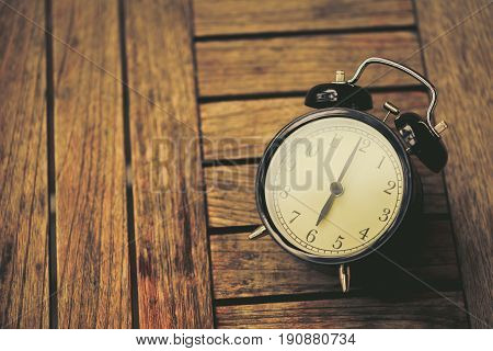 Old Clock At 6 O'clock On Wooden Table Vintage Color Tone.